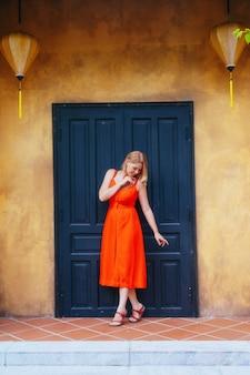 Красивая девушка в красном платье стоит напротив темной двери старого желтого дома с китайскими фонарями. архитектура древнего города хойан. вьетнам.