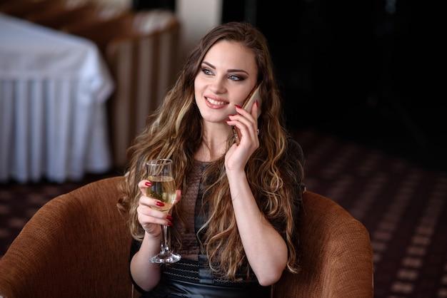 Красивая девушка в ресторане общается по телефону.