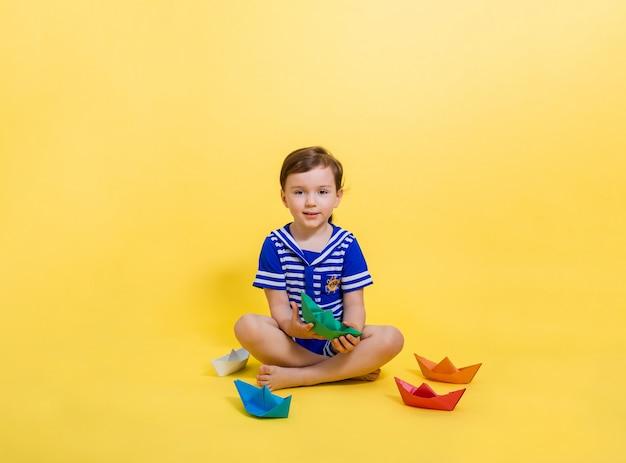 セーラー服を着た美しい少女は、カラフルな紙の船に座って、黄色い空間を見ます。