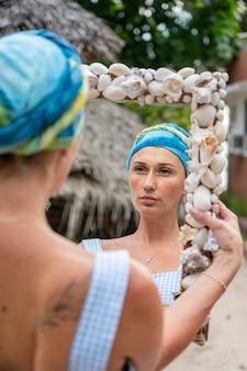 スカーフを着た美少女が鏡で自分を見つめ、クローズアップ
