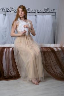 Красивая девушка в сексуальный халат, держа перо, сидя на белой ванне.