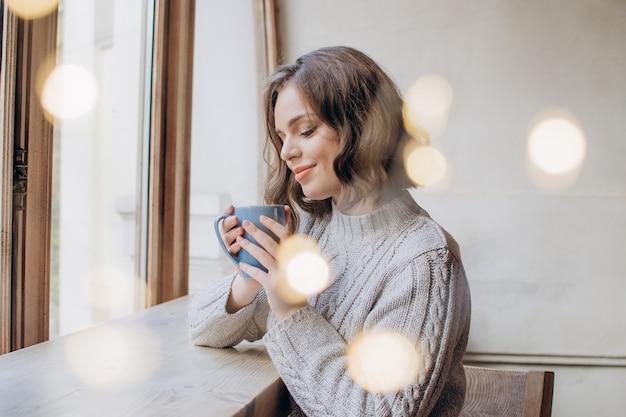 セーターを着た美しい少女は、窓とライトの背景にお茶やコーヒーを飲みます