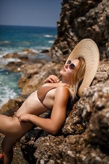 岩の多い海岸の近くに、帽子に金色の日焼けをした水着姿の美少女が立っています。海沿いの夏の晴れた日。休暇の概念