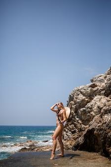 青い海の近くの岩だらけの海岸に沿って歩く帽子をかぶった金色の日焼けをした水着の美しい少女。海沿いの夏の晴れた日。休暇の概念