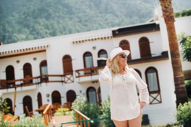 チュニックと帽子をかぶった美しい少女が美しい景色を望む別荘の近くに立っています。女性はトルコのリゾートで休日を楽しんでいます