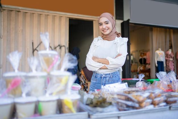 Красивая девушка в чадре со скрещенными руками продает различную еду, съеденную после прекращения поста