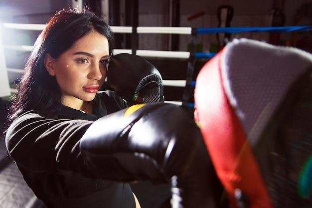 Красивая девушка в боксерских перчатках бьет лапами по рингу