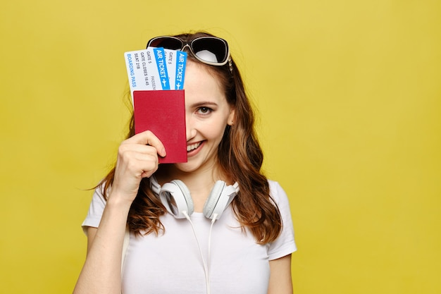 カジュアルな服装の美しい少女は、顔の半分をカバーするパスポートと航空券を持っています。