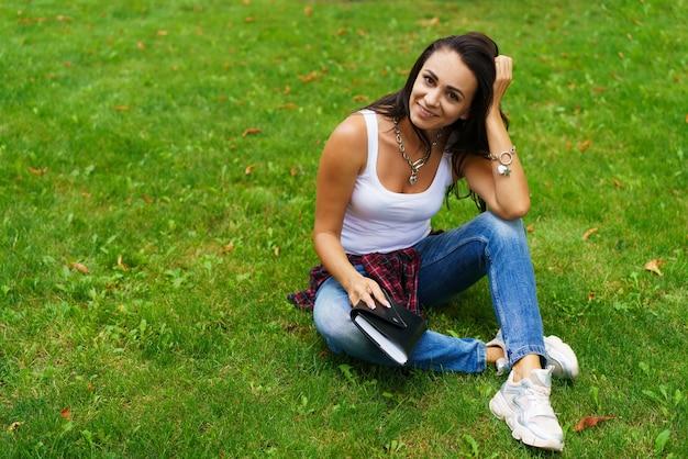평상복 차림의 아름다운 소녀가 대학 공원의 잔디에 메모장이 있는 메모장을 들고 앉아 있습니다.