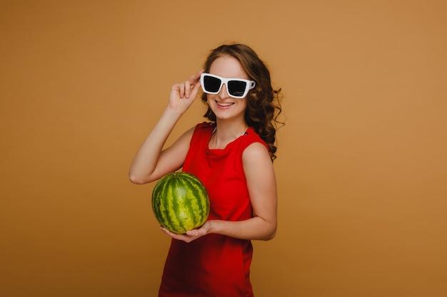 안경과 빨간 드레스의 아름다운 소녀는 그녀의 손에 수박을 보유하고 있습니다.