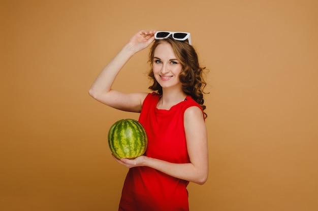 Красивая девушка в очках и красном платье держит в руках арбуз.