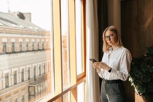 Красивая девушка в очках стоит у окна в офисе в руках с телефоном, набирающим текст.
