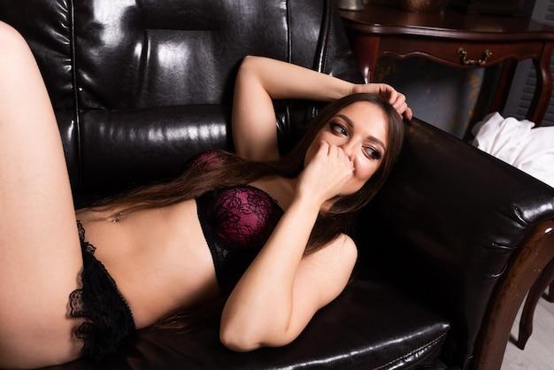란제리를 입은 아름다운 소녀가 가죽 소파에 누워 있습니다. 어떤 목적을 위해.