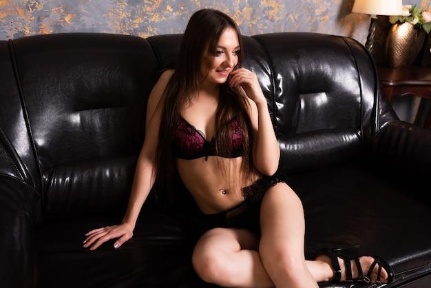란제리를 입은 아름다운 소녀가 검은 가죽 소파에 앉아 미소를 짓고 있습니다. 어떤 목적을 위해.