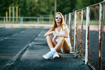 A beautiful  girl  in the sunglasses sitting near the fence on her skateboard.