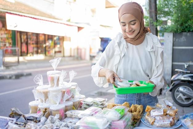 Красивая девушка в чадре с пластиковым подносом выбирает разные виды оладий для покупки