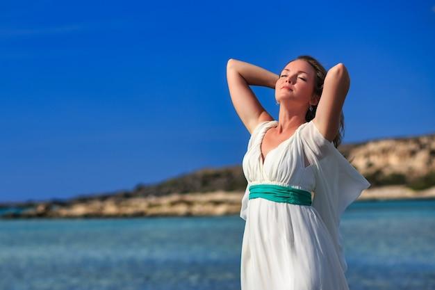하얀 드레스를 입은 아름다운 소녀가 신선한 바다 공기와 바다를 즐기며 그리스 엘라포니시 해변에 서 있습니다.