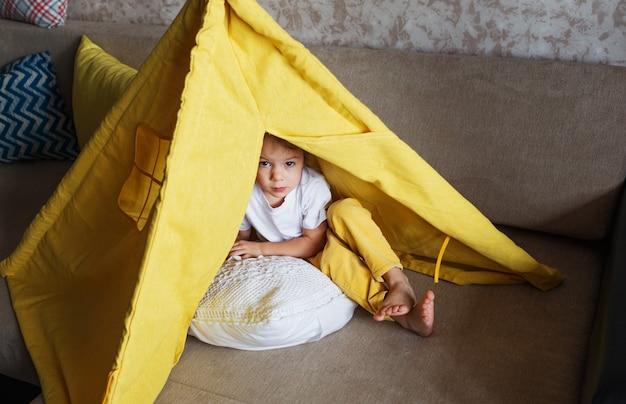 노란색 바지와 흰색 티셔츠를 입은 아름다운 소녀가 소파에서 집에서 천막 안쪽으로 놀아요. 어린이를위한 홈 게임