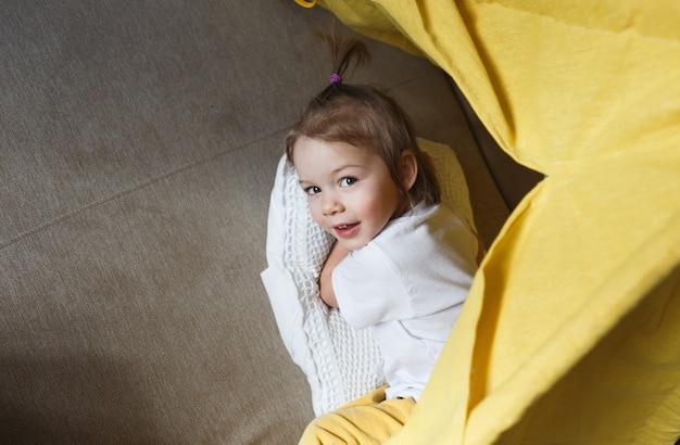 노란색 바지와 흰색 티셔츠를 입은 아름다운 소녀가 소파에 앉아 집에있는 천막 안에서 웃으며 놀아요. 어린이를위한 홈 게임