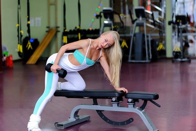 Красивая девушка занимается в тренажерном зале.