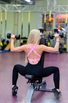 아름다운 소녀가 체육관에 종사하고 있습니다.