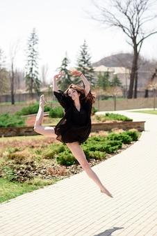 Красивая девушка занимается хореографией на природе.