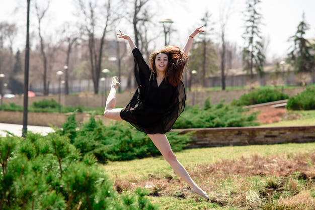 Красивая девушка занимается хореографией на природе