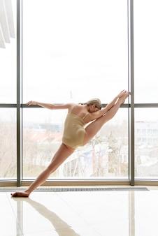 У большого окна красивая девушка занимается хореографией.