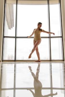 У окна красивая девушка занимается хореографией.