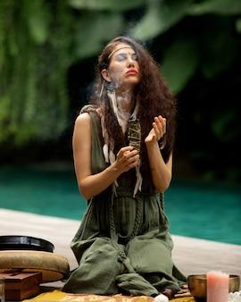 아름다운 소녀가 무속 행위에 종사하고 있습니다.