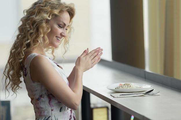 아름다운 소녀가 샐러드를 즐기고 있습니다. 오랜 기다림 끝에 여자를 위한 음식이 나왔다.