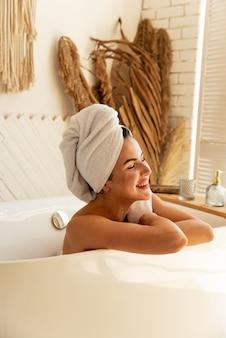 美しい少女がバスルームに横たわっています。彼女はお風呂の手順をすることによって楽しんで、自分の世話をします