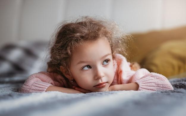 Красивая девушка лежит на диване и мечтает.