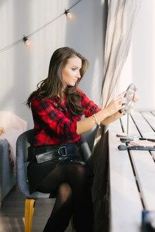 美しい少女は、窓際のテーブルミラーで自分を見ます。彼女の化粧をするつもり