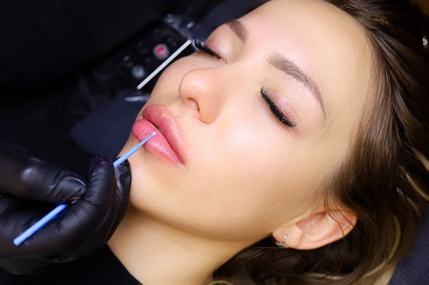 美しい少女モデルが唇のタトゥーの手順に横たわっていますマスターは小さなブラシで唇に麻酔をかけます