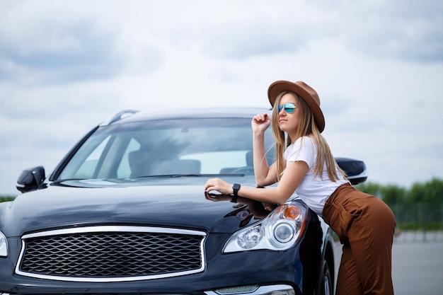 黒い車の近くに、眼鏡と茶色の帽子をかぶったヨーロッパ風の美しい少女が立っています。車の近くで写真撮影。