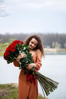 Красивая девушка европейской внешности с вьющимися волосами и улыбкой на лице с огромным букетом красных роз на фоне голубого озера. теплый летний день, счастливая молодая женщина, эмоции радости
