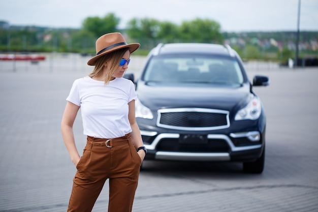 안경과 갈색 모자를 쓴 유럽풍의 아름다운 소녀가 검은색 차 옆에 서 있습니다. 주차장에 차를 가진 젊은 여자