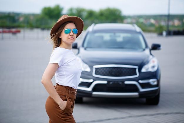 Возле черной машины стоит красивая девушка европейской внешности в очках и коричневой шляпе. молодая женщина с автомобилем на стоянке