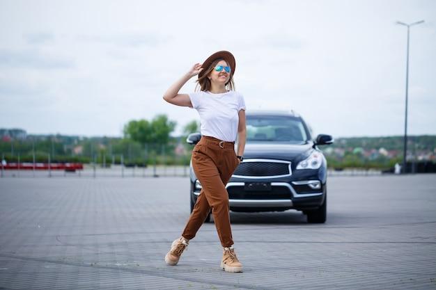 眼鏡と茶色の帽子をかぶったヨーロッパの外観の美しい少女が黒い車の近くに立っています。駐車場で車を持つ若い女性