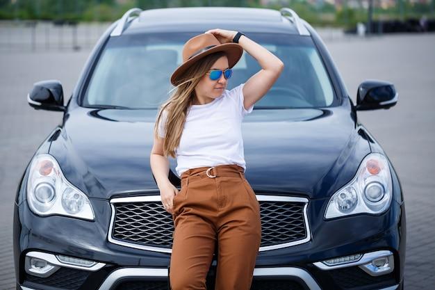 안경과 갈색 모자를 쓴 유럽풍의 아름다운 소녀가 검은색 차 옆에 서 있습니다.
