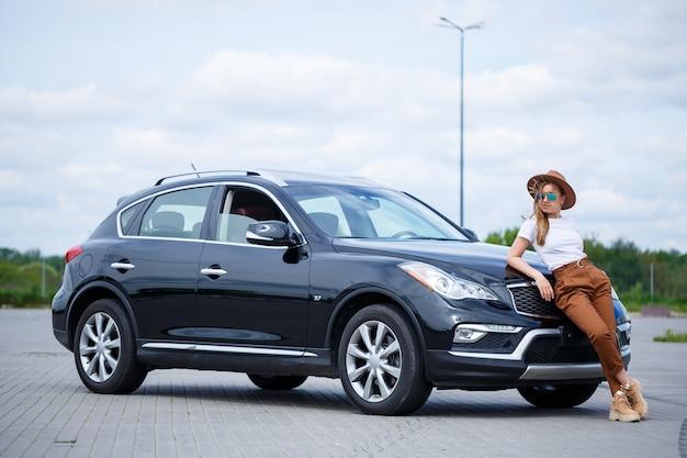Возле черной машины стоит красивая девушка европейской внешности в очках и коричневой шляпе.
