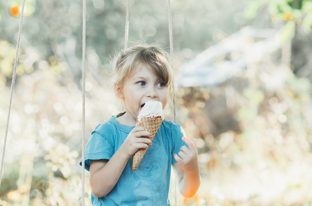 Красивая девочка пяти лет, ест мороженое на открытом воздухе, сидит на качелях, конус с фруктами