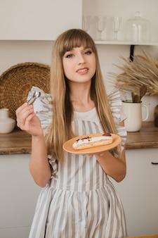 Красивая девушка кондитер или домохозяйка держит тарелку с эклерами и кондитерскими щипцами