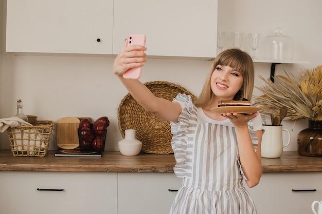 아름다운 소녀 페이스트리 셰프나 주부가 전화로 셀카를 찍는 요리 블로그 개념