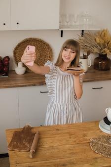 Красивая девушка кондитер или домохозяйка делает селфи по телефону концепция кулинарного блога