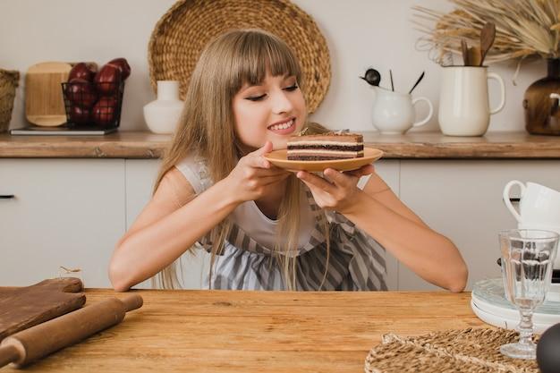 美しい少女のパティシエや主婦がデザートと一緒にキッチンに座って、思慮深く見えます