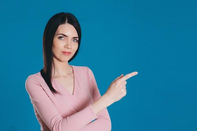 Красивая девушка указывает пальцем. модель на синем фоне. копировать пространство. рекламный баннер