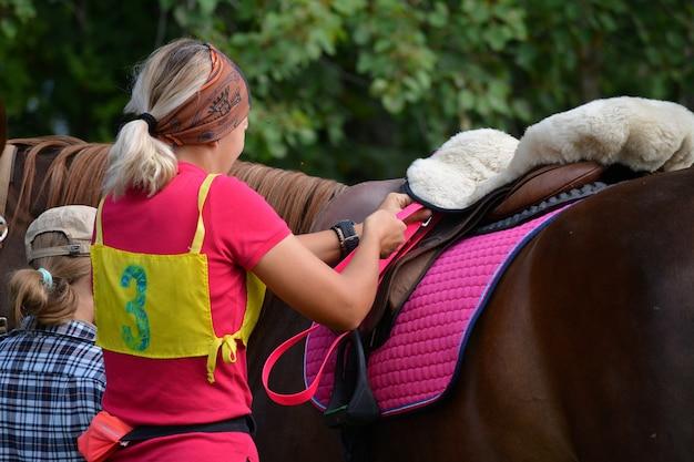 美しい少女が馬を競技に向けて準備します。