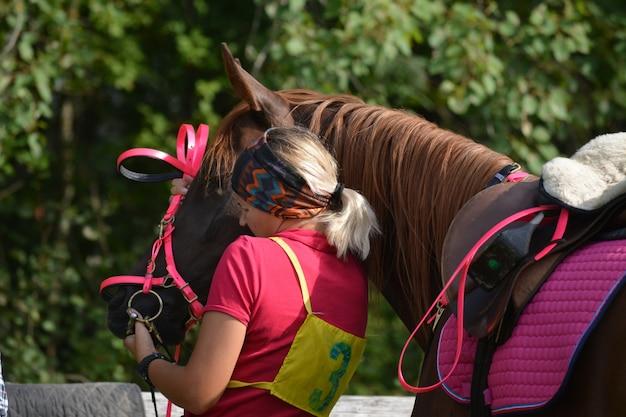 Красивая девушка надевает уздечку на свою лошадь.